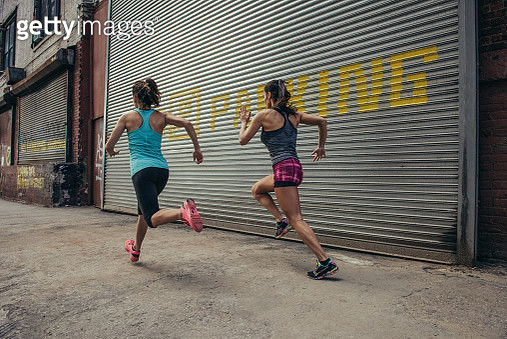 Two female runners running in city street - gettyimageskorea