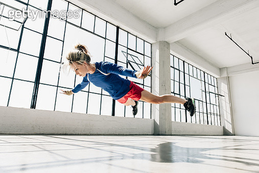 Low angle view of young woman in gym doing mid air push up - gettyimageskorea
