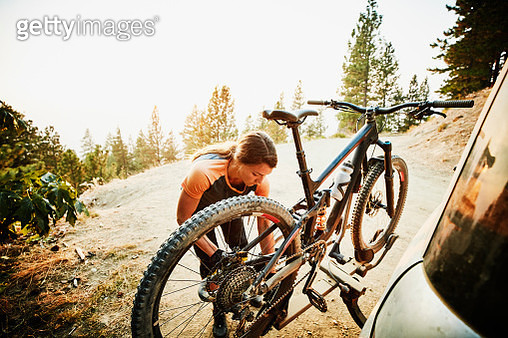 Female mountain biker putting bike on car after ride on summer evening - gettyimageskorea