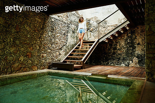 Woman descending stairs to spa at luxury resort - gettyimageskorea