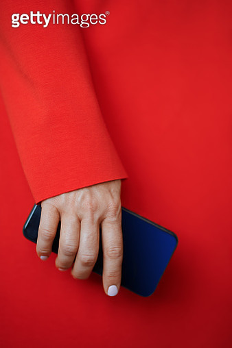 Woman in the red jacket or coat holding smartphone. Nicely fits for book cover - gettyimageskorea