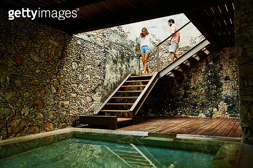 Couple descending stairs at spa in luxury resort - gettyimageskorea