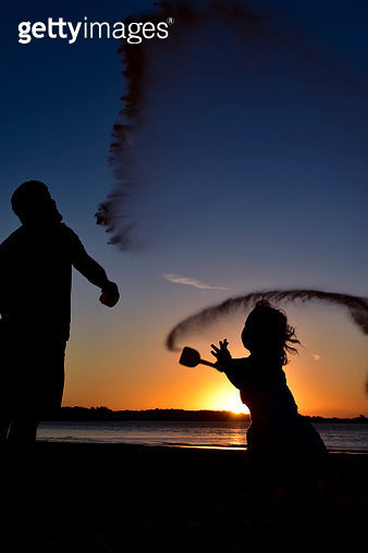 Silhouette Father And Daughter Throwing Sand At Beach Against Sky During Sunset - gettyimageskorea