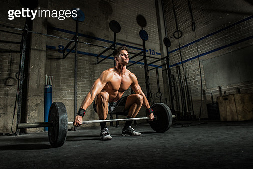 Young man squatting to lift barbell in gym - gettyimageskorea