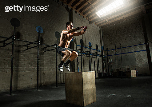 Young man jumping from wooden box in gym - gettyimageskorea