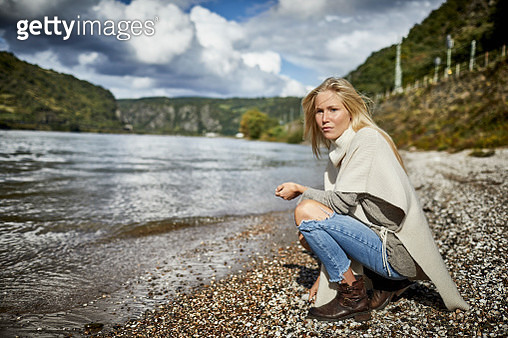 Blond young woman crouching at the riverbank - gettyimageskorea