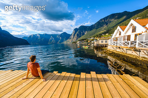 Man sitting on wooden pier admiring a Norwegian Fjord, Western Norway - gettyimageskorea
