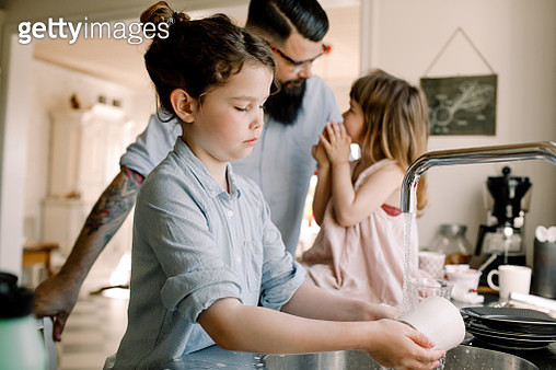 Girl washing mug at sink while father talking to daughter in kitchen - gettyimageskorea