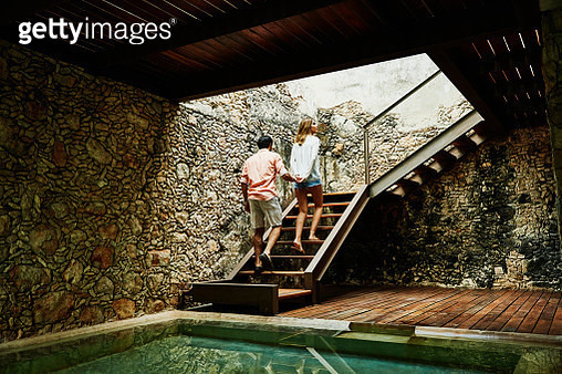 Couple holding hands while ascending stairs to room at luxury resort - gettyimageskorea