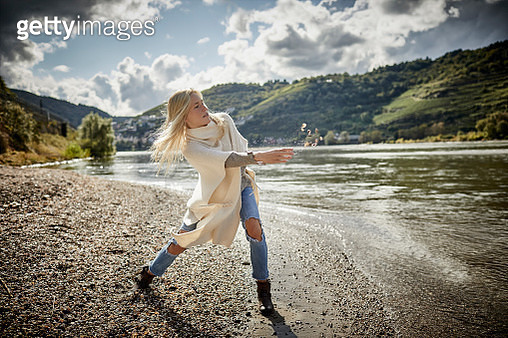 Blond young woman throwing mussels at the riverbank - gettyimageskorea