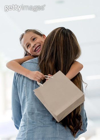 Happy girl hugging her mother at the shopping center - gettyimageskorea