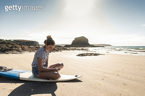 Young woman on the beach, sitting on surfboard, using smartphone - gettyimageskorea