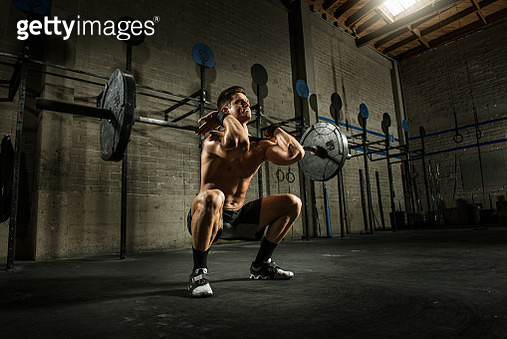Young man squatting with heavy barbell in gym - gettyimageskorea