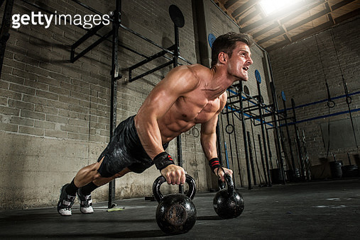 Young man performing press ups on kettlebells in gym - gettyimageskorea