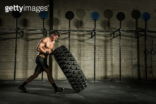 Young man lifting large tyre in gym - gettyimageskorea