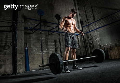Young man dropping barbell in gym - gettyimageskorea