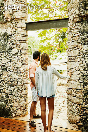 Couple standing in doorway to courtyard pool at luxury resort - gettyimageskorea