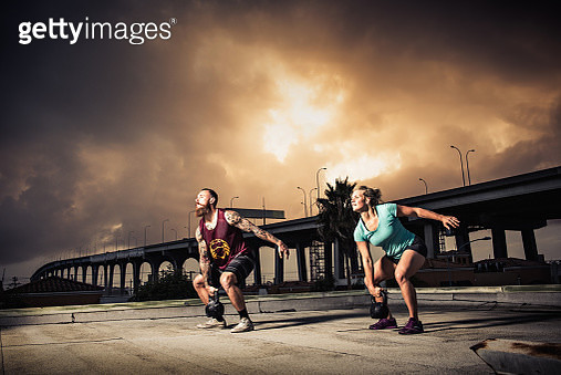 Man and woman training with kettlebells on gymnasium rooftop - gettyimageskorea