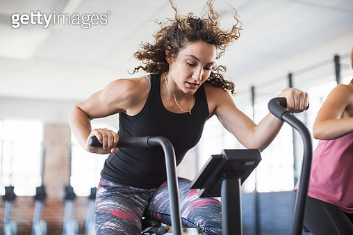 Determined young woman riding elliptical bike in gym - gettyimageskorea