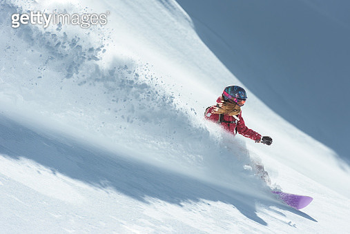 Young woman snowboarding in fresh snow - gettyimageskorea