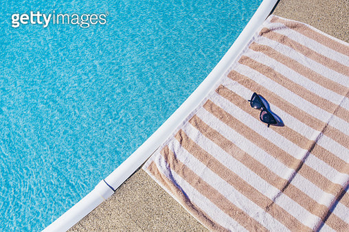 Summer Background: Striped Beach Towel With Cateye Sunglasses Next To Swimming Pool - gettyimageskorea