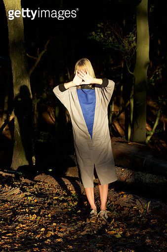 Portrait woman covering face in woods - gettyimageskorea