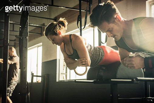 Man and woman training together in gymnasium - gettyimageskorea