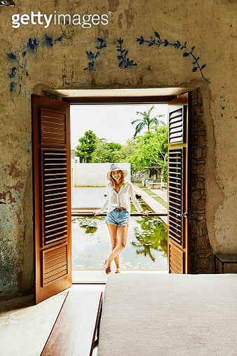 Smiling woman in sun hat standing on balcony of room at tropical luxury resort - gettyimageskorea