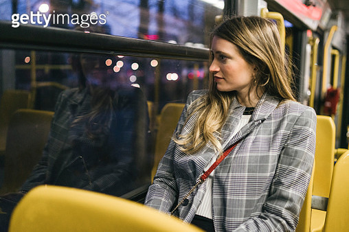 Young woman with long blond hair looking out through train carriage window at dusk - gettyimageskorea