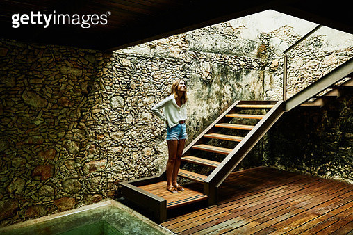 Smiling woman standing at bottom of stairs at luxury resort looking up - gettyimageskorea