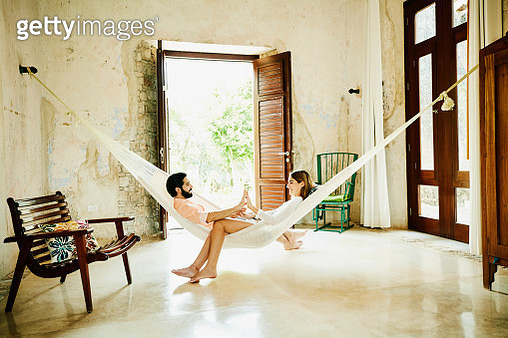 Smiling couple holding hands while relaxing in hammock in room at luxury resort - gettyimageskorea