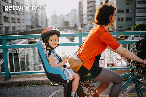 Mother cycling with her little girl in urban city, Tokyo - gettyimageskorea