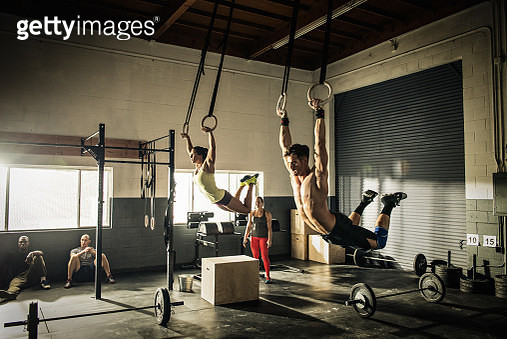 Man and woman training on gymnasium rings - gettyimageskorea