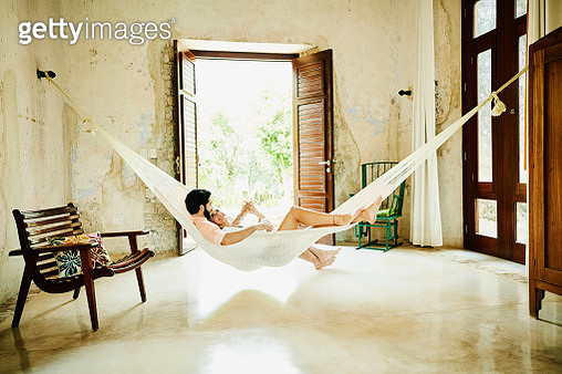 Smiling couple relaxing together in hammock in room at luxury resort - gettyimageskorea