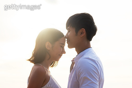 Young asian couple or lover kiss on the beach with evening light. Young lovers on vacation - gettyimageskorea