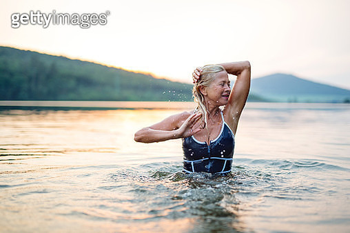 Active senior woman standing in water in lake outdoors in nature. Copy space. - gettyimageskorea
