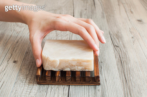 A close-up of a female hand holding a white organic soap - gettyimageskorea