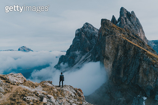 Young Caucasian man  hiking near Seceda mountain in Dolomites - gettyimageskorea