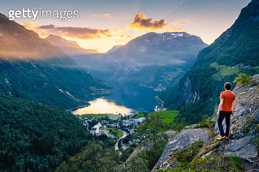 Man admiring Geiranger and the Geirangerfjord at sunset, Norway - gettyimageskorea