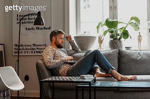Man on sofa using laptop - gettyimageskorea