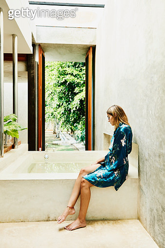 Woman in bathrobe sitting at edge of bathtub - gettyimageskorea