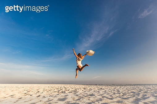Playful woman having fun while jumping high-up on the beach with her arms raised. Copy space. - gettyimageskorea