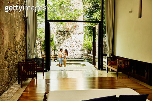 Embracing couple standing in plunge pool outside of room at luxury tropical resort - gettyimageskorea