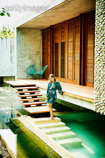 Smiling woman in bathrobe standing at edge of plunge pool outside of bungalow at luxury tropical resort - gettyimageskorea