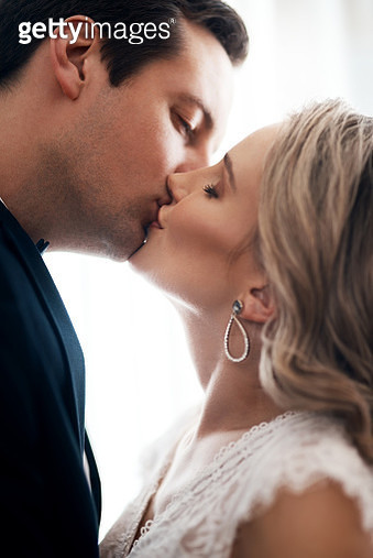 Cropped shot of an affectionate young couple standing indoors together and kissing after their wedding - gettyimageskorea