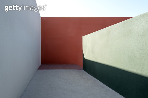 Corridor composed of colored concrete walls, with sunlight effect - gettyimageskorea