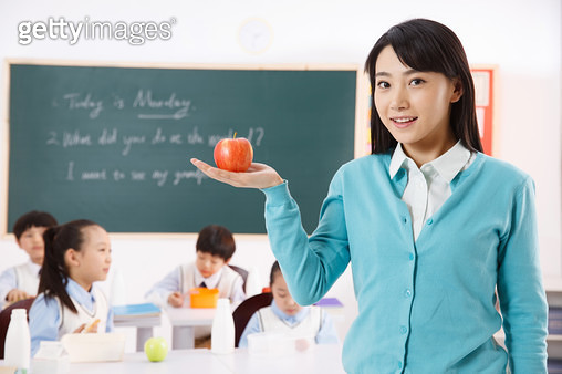 The teacher took the apple in the classroom - gettyimageskorea