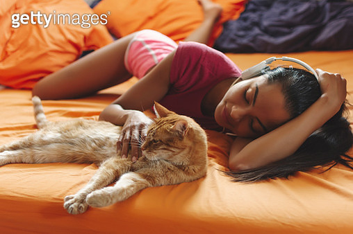 Happy woman at home listening music and cuddle her cat - gettyimageskorea