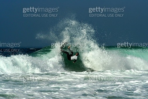 Lisbon, Portugal - October 2009: Surfer surprised by a closing wave falls from his surfboard. He is falling backwards into the wave trying to catch himself with one arm. The water sprays all around him. - gettyimageskorea