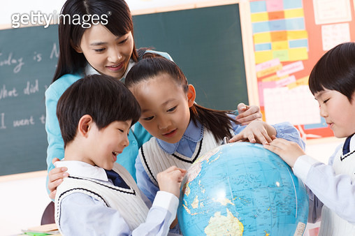 The teacher and pupil look at a globe in the classroom - gettyimageskorea